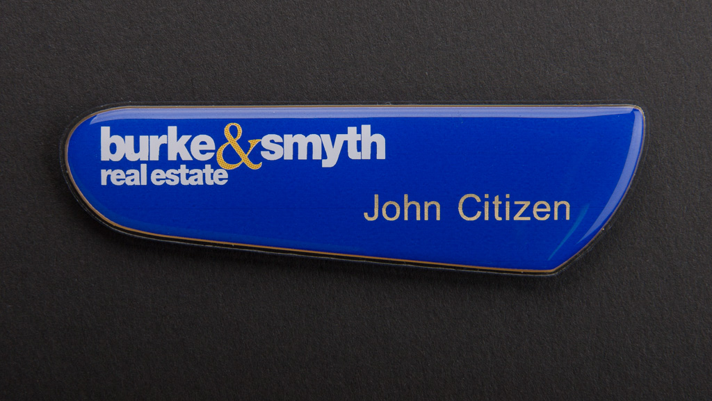 A blue real estate name badge