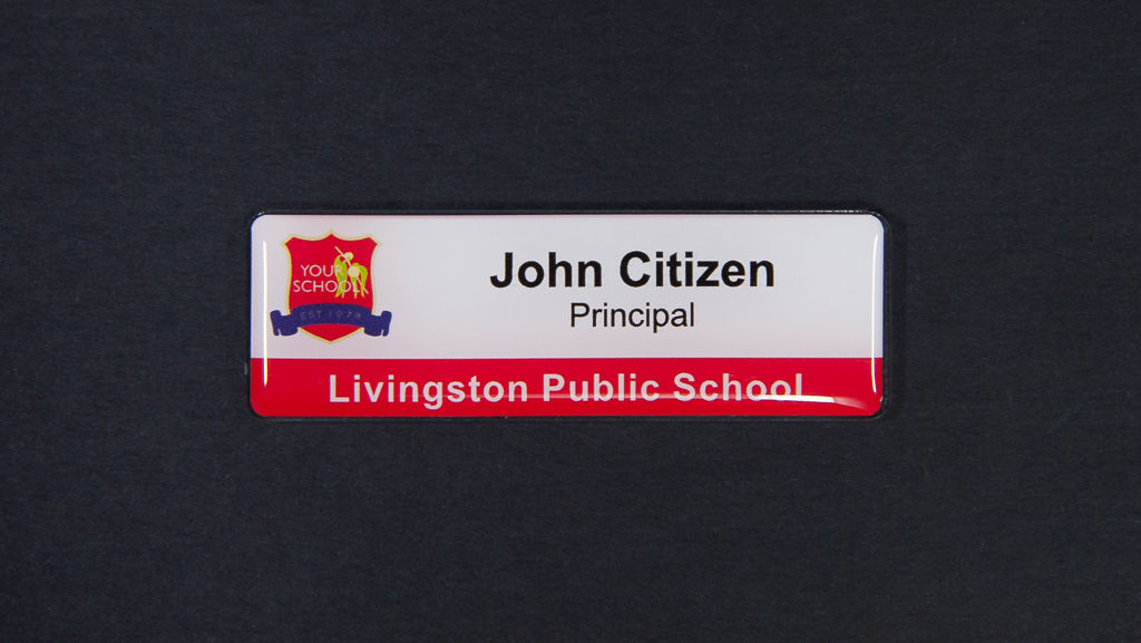 A white and red name badge for Livingston Public School