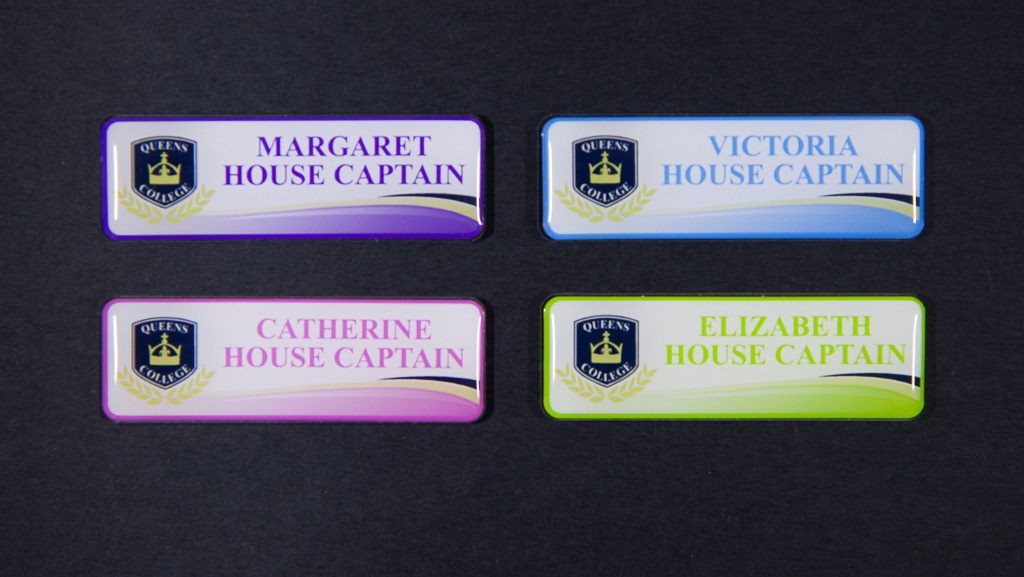 Four house captain badges in purple, blue, pink and green
