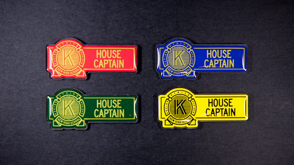 Four house captain name badges that are red, blue, green and yellow