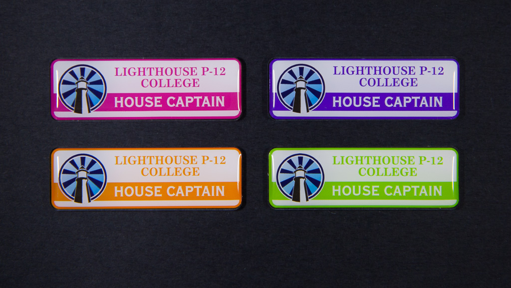 Four house captain badges with a round blue logo