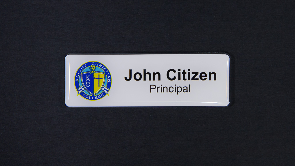 A name badge that is mostly white and the text is black with a blue logo on the left