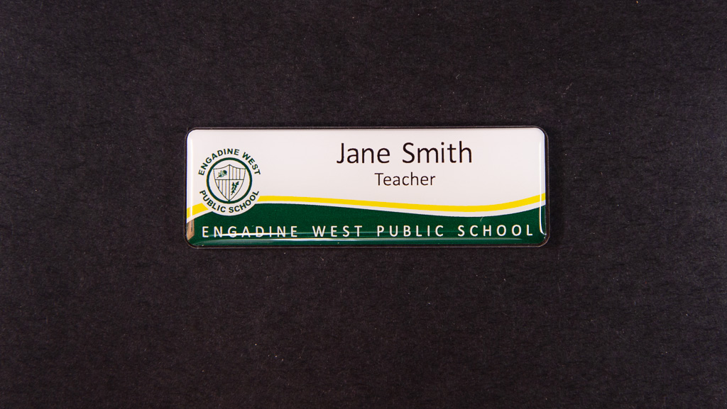 A green and white name badge for a public school