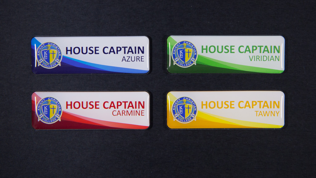 Four house captain badges in blue, green, red and yellow