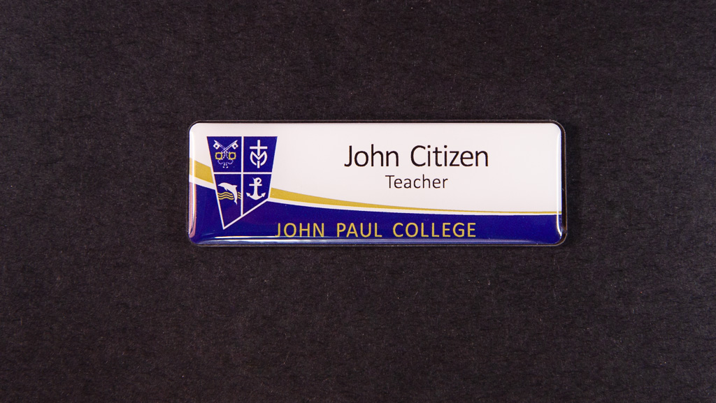 A teacher's white and blue name tag
