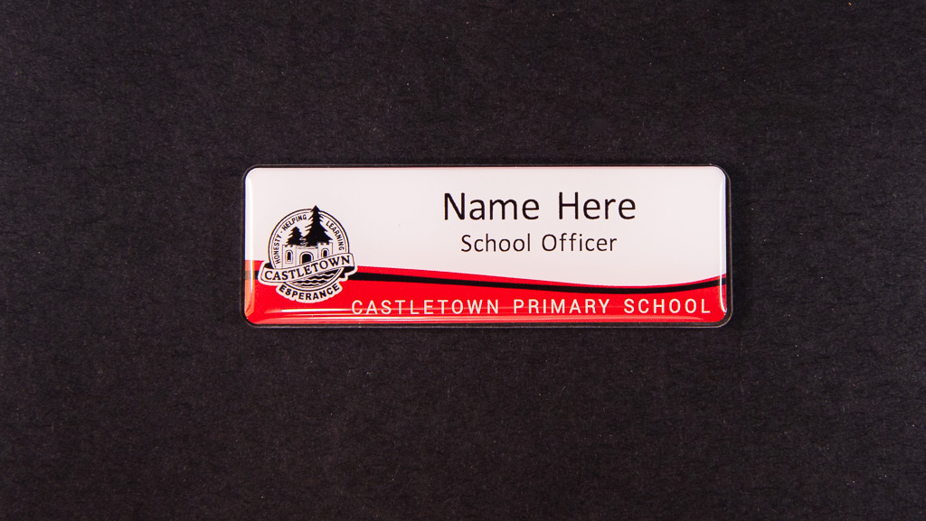 A white and red name badge for a primary school