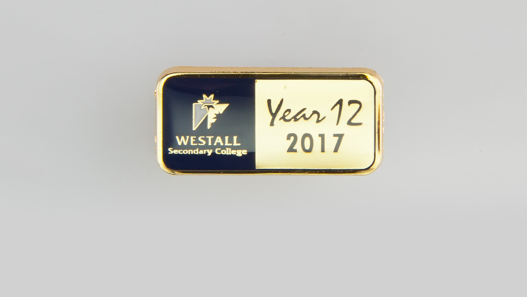 A custom designed in Australia metal badge for a year 12 class. It is gold with navy and features the school's logo.