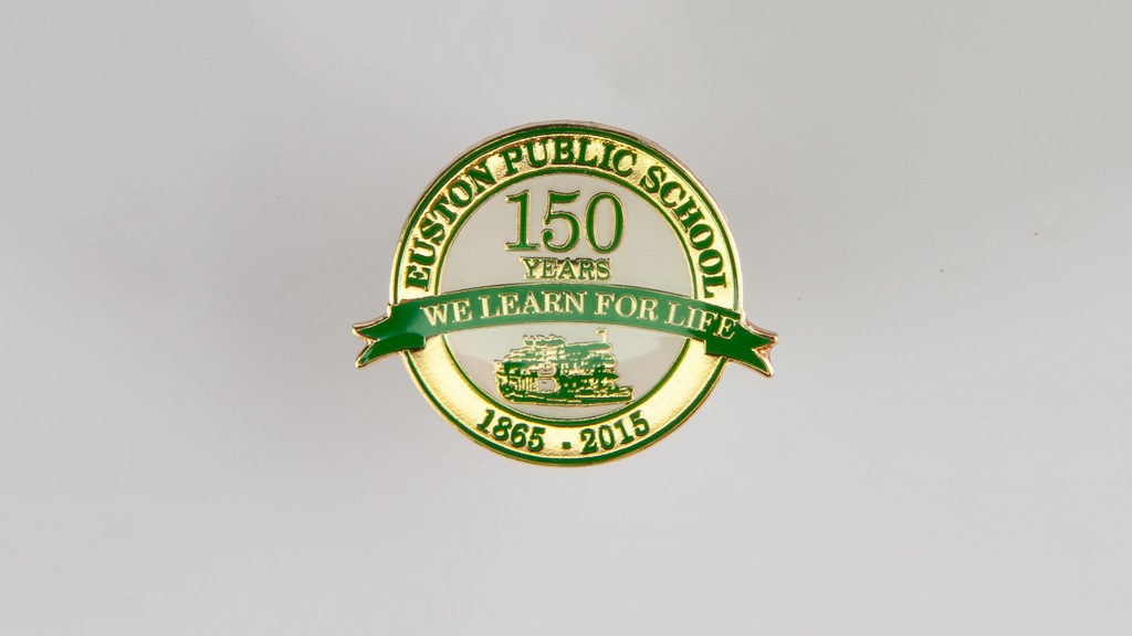 Green and gold custom metal shaped badge to celebrate 150 years.