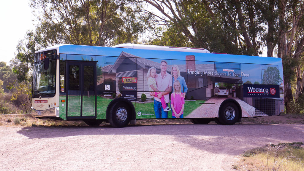 Massive body wrap on a bus. White family pictured in front of an Australian house.