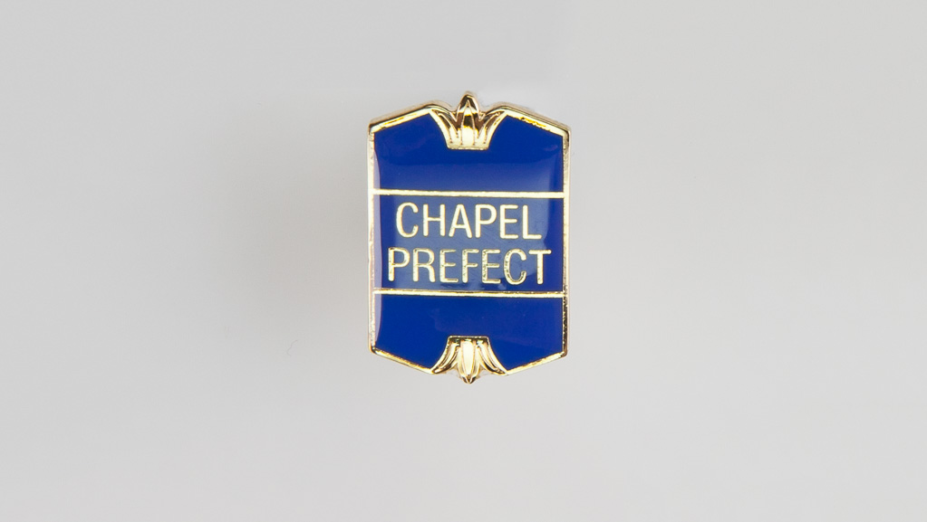 "A simple golden ""Chapel Prefect"" metal pin."