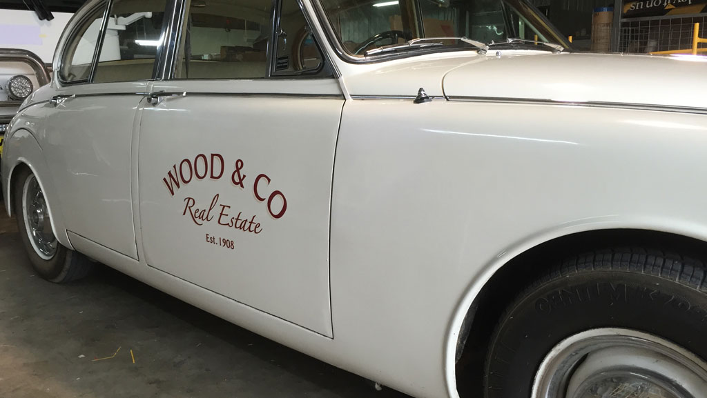 Cropped in photo of a classic car with custom vehicle graphics.