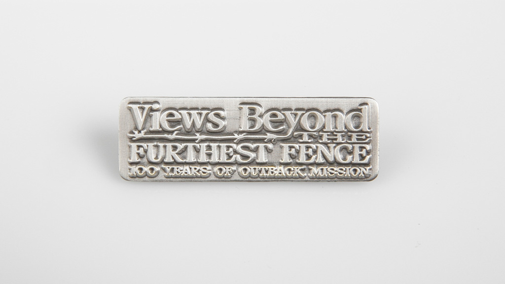 A custom manufactured commemorative metal badge.
