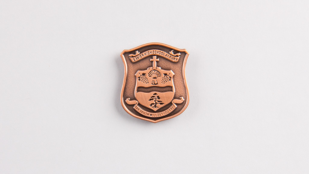 Custom bronze coloured metal badge.