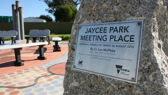 A custom made outdoor plaque mount on a big rock in a park.