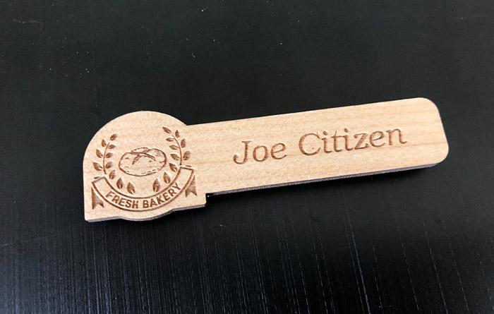 Custom shaped wooden name badge with laser engraved logo