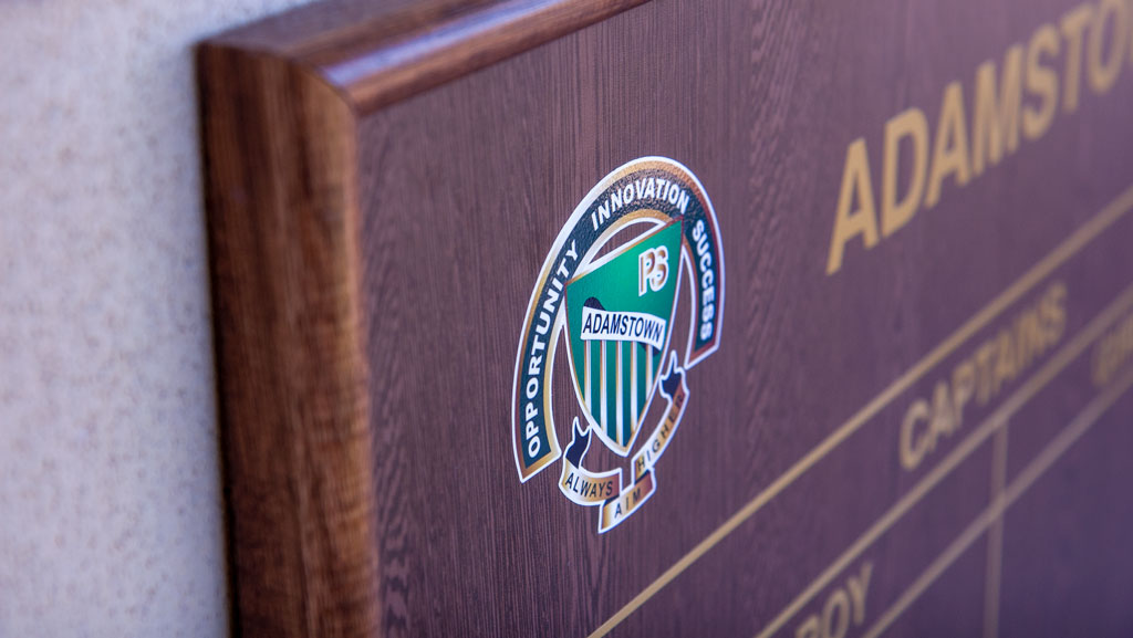 Close up photo of a wooden honour board, showing a full colour logo for Adamstown Public School.