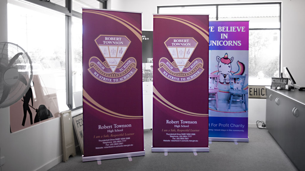 Two roll up banners for a school and another pull up banner in the background for a charity.