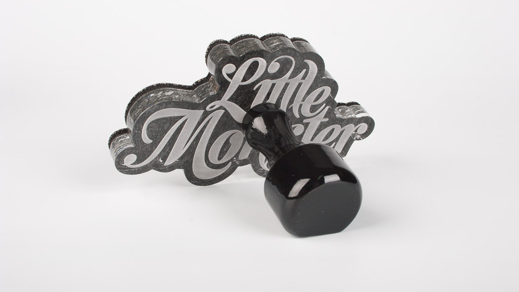 3/4 photo of a custom rubber stamp with a traditional wooden handle.