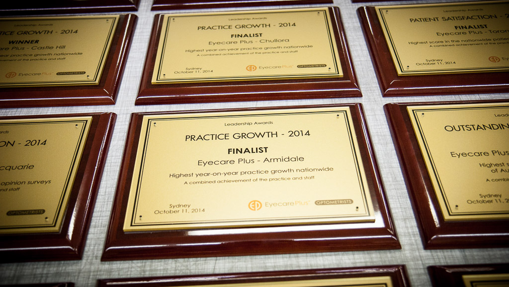 Several custom made corporate award plaques. Digital printed gold vinyl behind acrylic award plaque.
