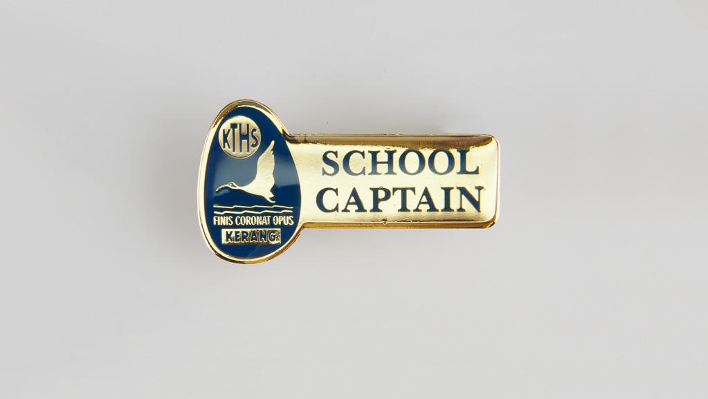 A golden colour custom made School Captain badge with epoxy.