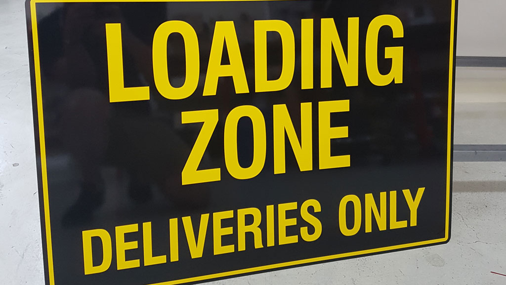 Loading Zone Deliveries Only sign. Yellow text with a black background.