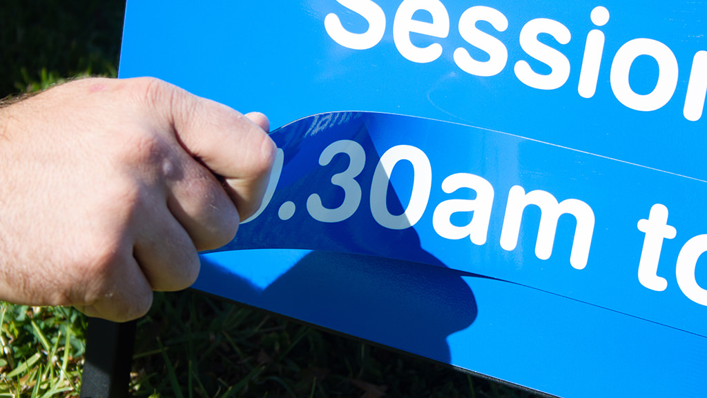 A hand showing that you can change the times on this A Frame as it is a magnetic sign.