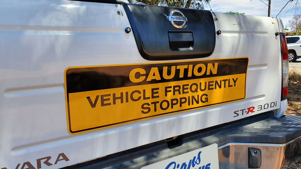 "A yellow ""CAUTION VEHICLE FREQUENTLY STOPPING"" magnetic sign on the rear of a ute."