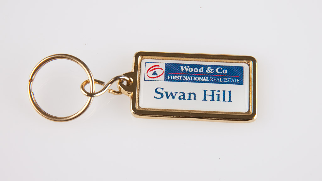 Gold coloured key tag with a domed sticker of the company details.