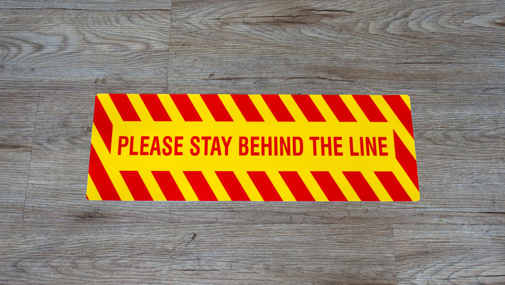 Please stay behind the line floor decal.
