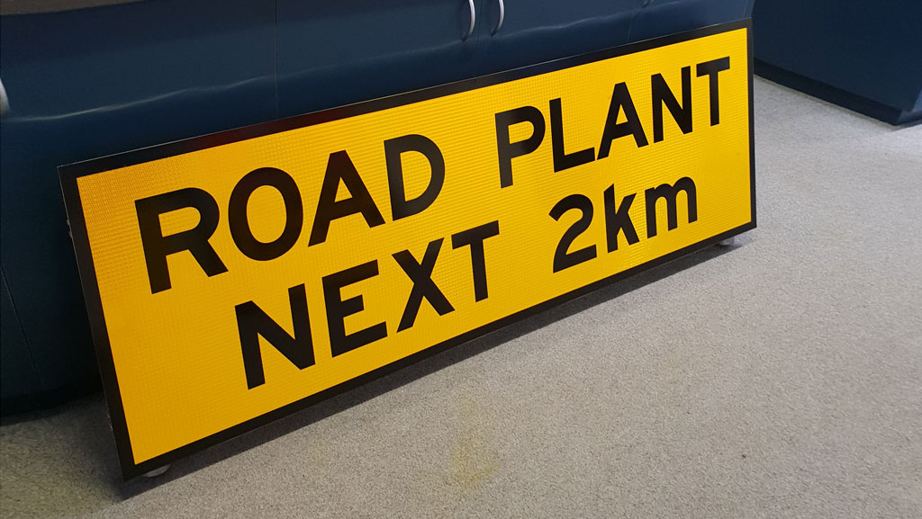 Road Plant Next 2km safety sign.