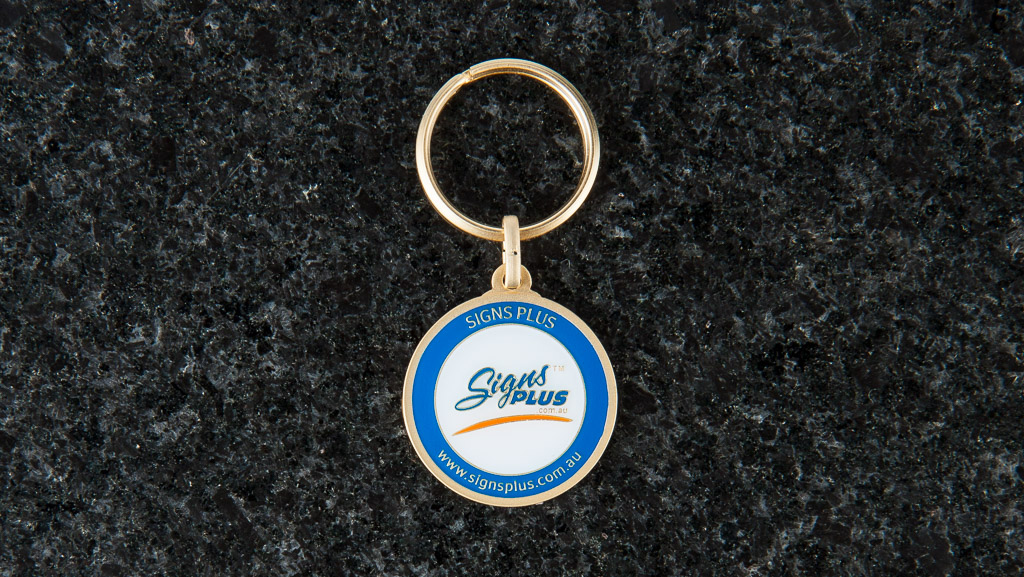 Sandblast, hard enamel logo on a round metal key tag.