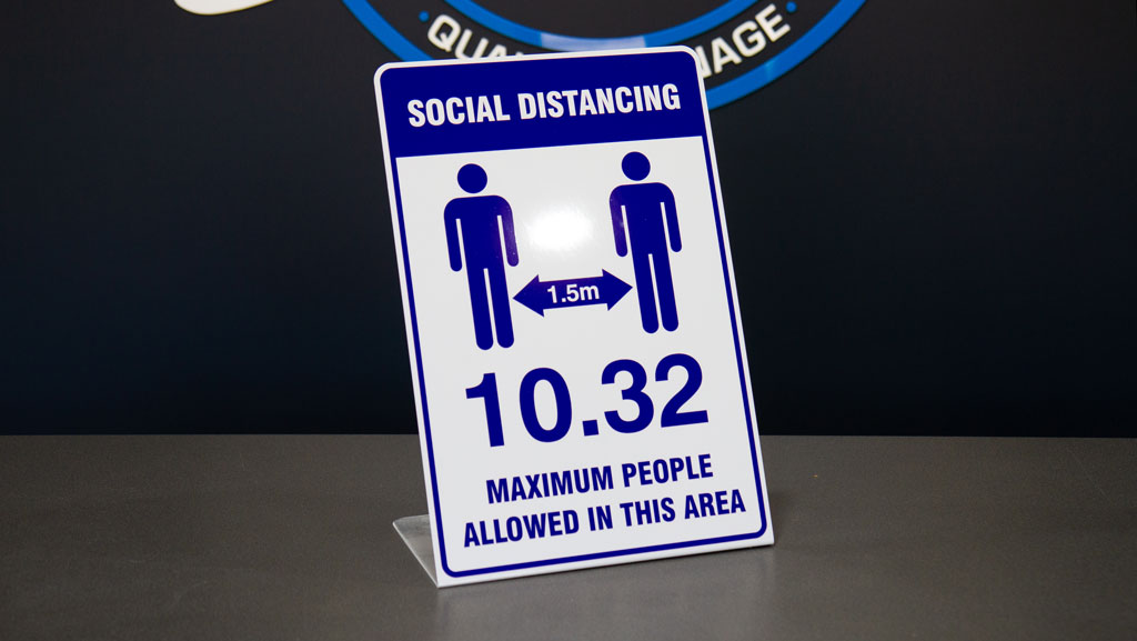 A freestanding social distancing sign that explains the maximum of people allowed in an area/shopfront.