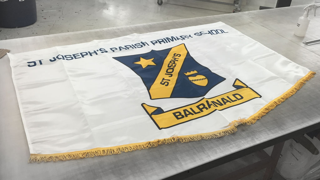 A custom made marching banner. It is mostly white with a school logo on the front. It also features a golden coloured frill along the bottom edge.