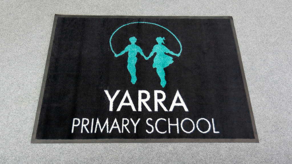 A black custom manufactured logo mat for the Australian Yarra Primary School