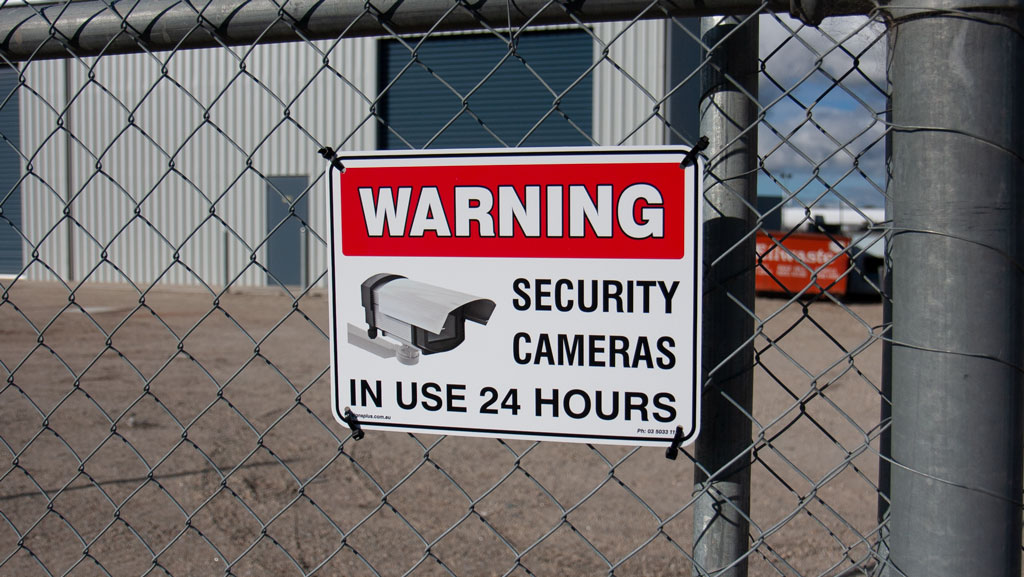 Warning Security Cameras In Use 24 Hours safety sign mounted on a fence.