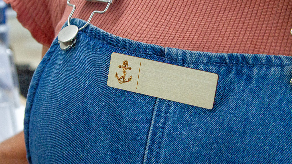 Custom wooden name badge with a magnetic clip on a persons trendy denim overalls.