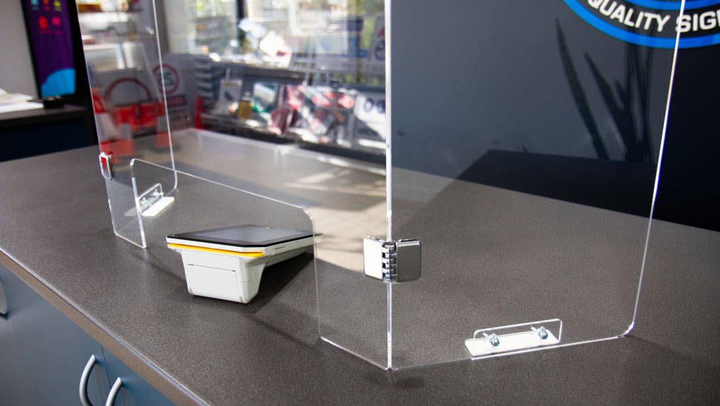 The collapsible sneeze guard pictured with the new metal hinges sitting on a shop counter.