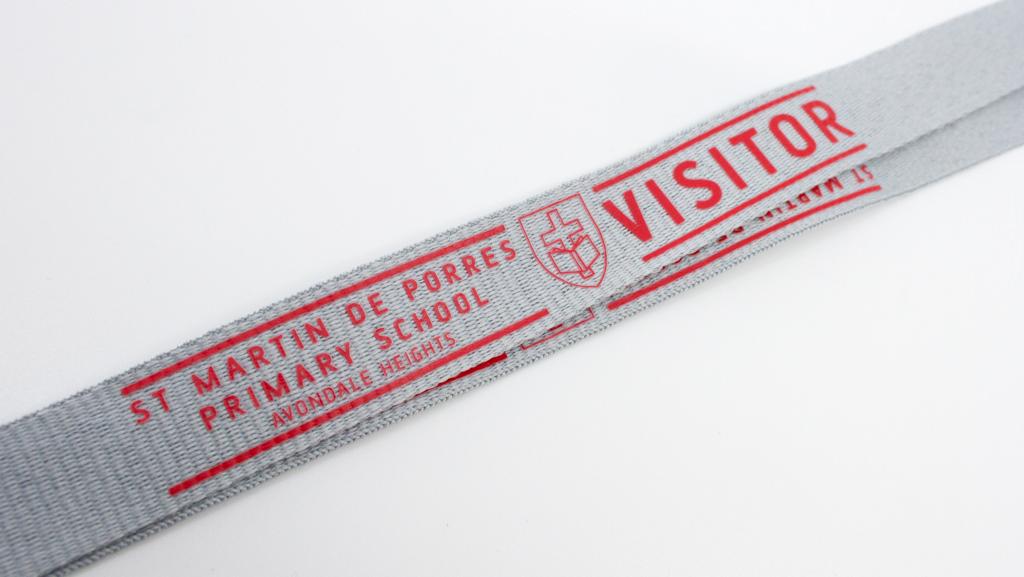Custom visitor lanyard with school logo. Red design on light grey.