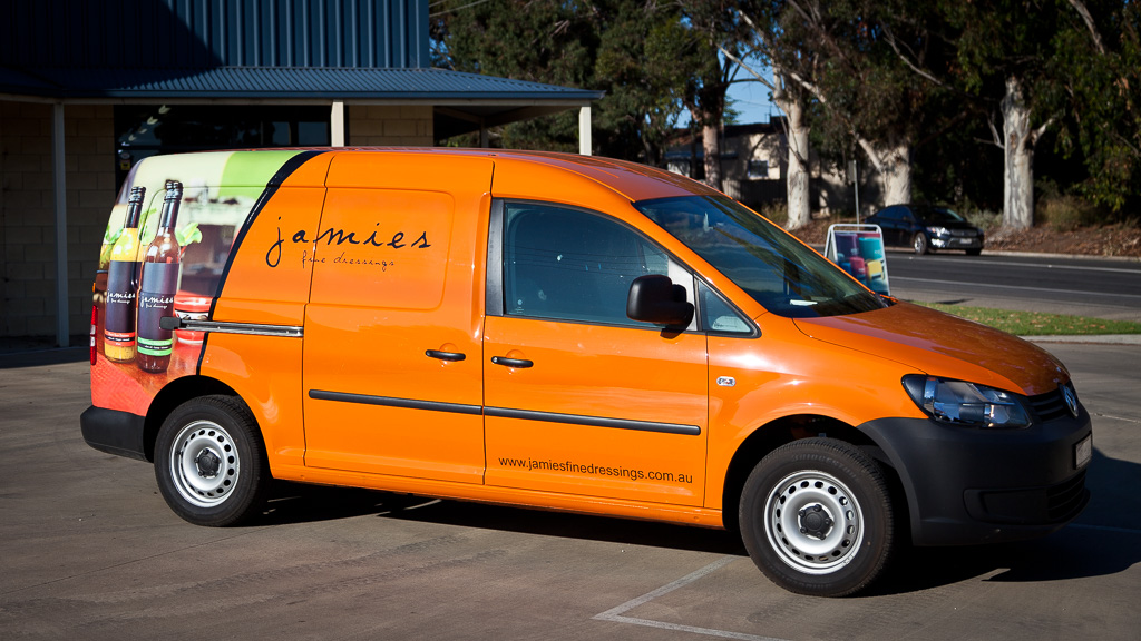 Volkswagon Caddy van in orange witha partial body wrap and custom graphics advertisement.